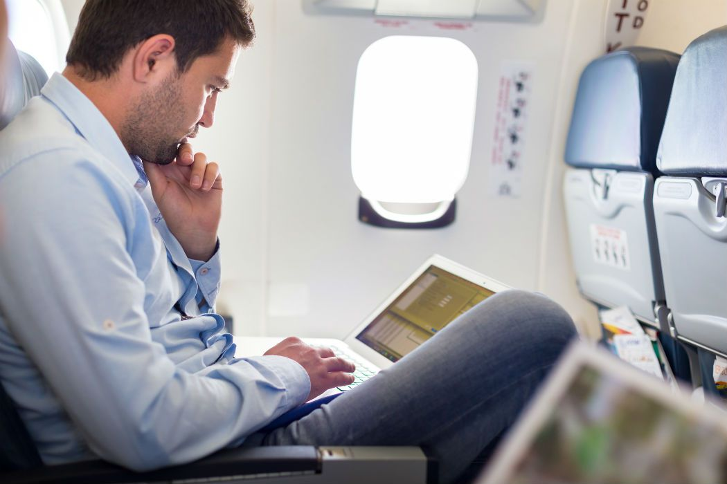 Businessman-working-with-laptop-on-airplane